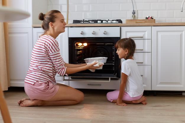 Portret van een gelukkige jonge vrouw die bakken uit de oven haalt, haar dochter kijkt naar lekkere snoepjes, mensen die casual kleding dragen, zittend op de vloer in de keuken, samen koken.