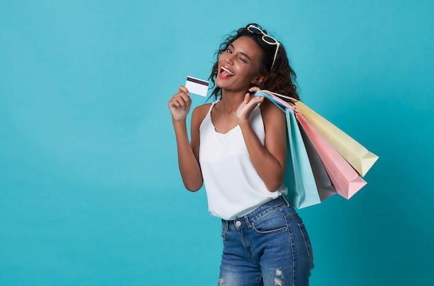 Portret van een gelukkige jonge vrouw die creditcard en het winkelen zak toont die over blauwe achtergrond wordt geïsoleerd.