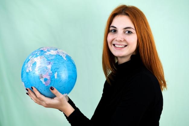 Portret van een gelukkige jonge vrouw die de geografische bol van de wereld in haar handen houdt. reisbestemming en planeetbeschermingsconcept.