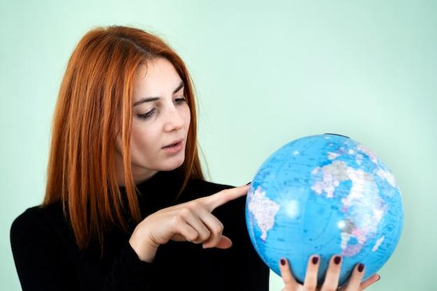 Portret van een gelukkige jonge vrouw die de geografische bol van de wereld in haar handen houdt