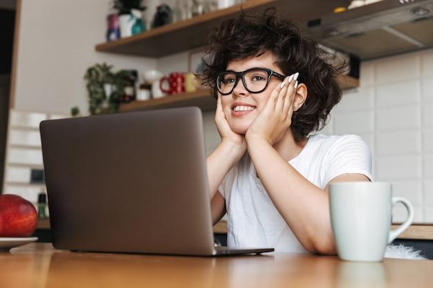 Portret van een gelukkige jonge vrouw die een bril draagt die 's ochtends op de laptop werkt