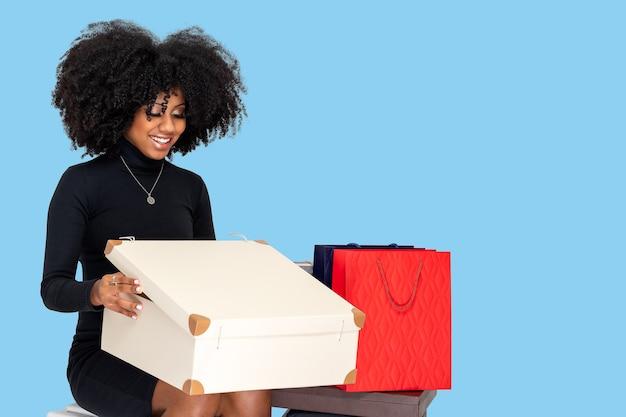 Portret van een gelukkige jonge vrouw die een geïsoleerde aankoopdoos op een blauwe achtergrond houdt