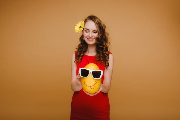 Portret van een gelukkige jonge vrouw die een meloen met glazen houdt. meloen met een glimlach.
