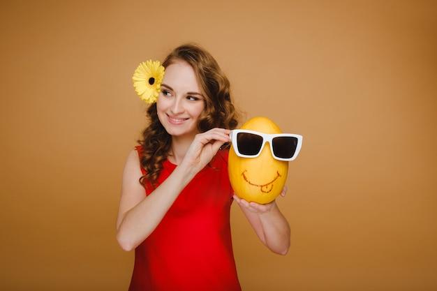 Portret van een gelukkige jonge vrouw die een meloen met glazen houdt