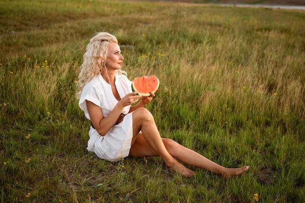 Portret van een gelukkige jonge vrouw die geniet van en watermeloen eet in de buitenlucht, het langzame leven van de zomerlevens...