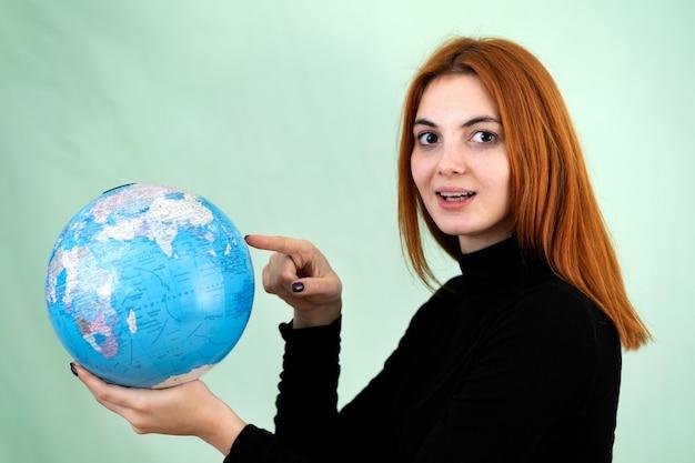 Portret van een gelukkige jonge vrouw die geografische wereld van de wereld in haar handen. reisbestemming en planeetbescherming concept.