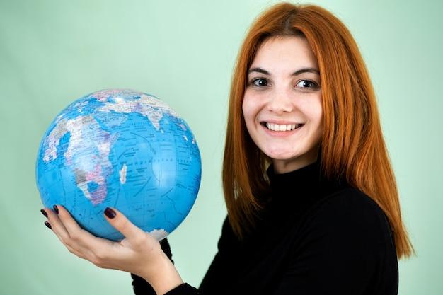 Portret van een gelukkige jonge vrouw die geografische wereld van de wereld in haar handen