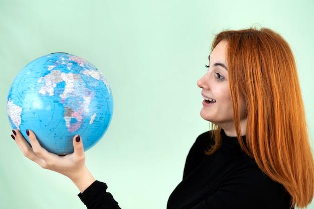 Portret van een gelukkige jonge vrouw die geografische wereldbol