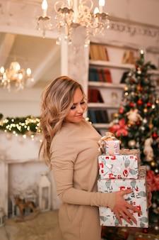 Portret van een gelukkige jonge vrouw die heel wat geschenkdozen op de achtergrond van een kerstboom houdt