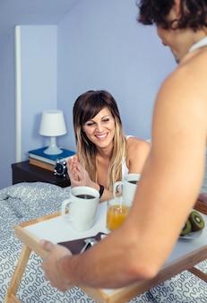 Portret van een gelukkige jonge vrouw die in bed zit en naar het ontbijt kijkt in een dienblad geserveerd door een knappe man. paar huis levensstijl concept.