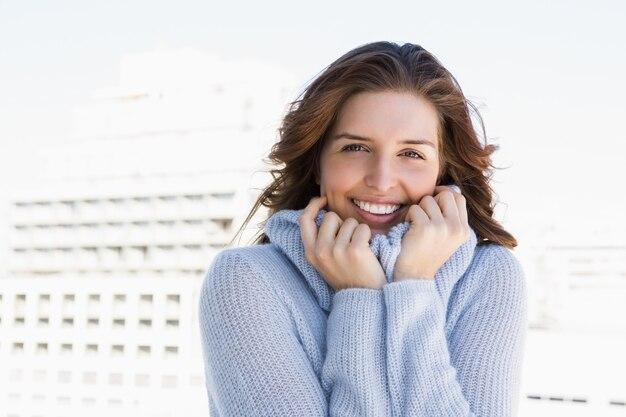 Portret van een gelukkige jonge vrouw die in koude rilt
