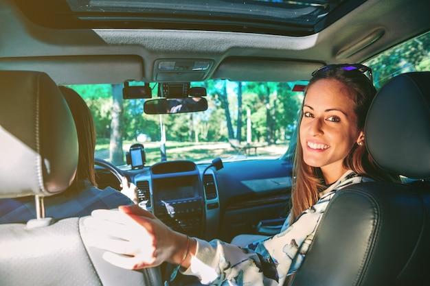 Portret van een gelukkige jonge vrouw die lacht terwijl ze in de auto zit terwijl haar vriend in een roadtrip-avontuur rijdt. vrouwelijke vriendschap en vrije tijd concept.