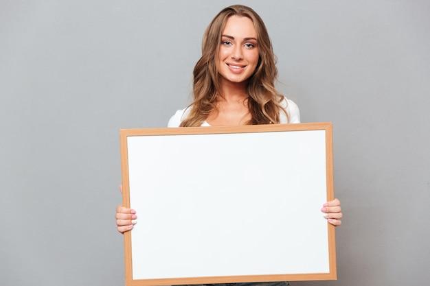 Portret van een gelukkige jonge vrouw die leeg bord houdt dat op een grijze muur wordt geïsoleerd