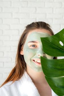 Portret van een gelukkige jonge vrouw die met een gezichtsmasker een monsterablad houdt