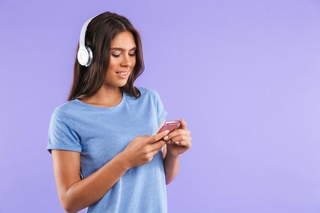 Portret van een gelukkige jonge vrouw die mobiele telefoon houdt