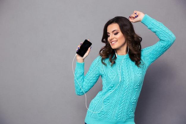 Portret van een gelukkige jonge vrouw die muziek luistert in een koptelefoon en danst over een grijze muur