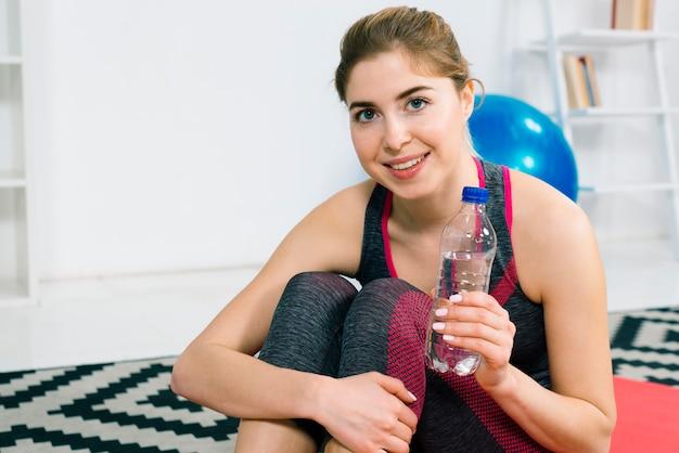 Portret van een gelukkige jonge vrouw die plastic waterfles houdt