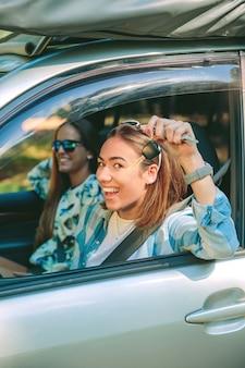 Portret van een gelukkige jonge vrouw die sleutels van een nieuwe auto toont met haar vriend klaar om een reis te beginnen. vrouwelijke vrije tijd concept.
