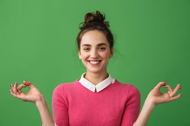 Portret van een gelukkige jonge vrouw die zich geïsoleerd over groen, mediteren bevindt