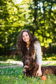 Portret van een gelukkige jonge vrouw en haar hond in tuin