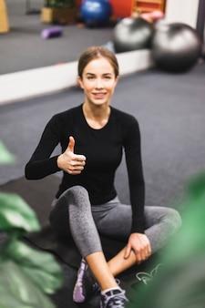 Portret van een gelukkige jonge vrouw gesturing duimen omhoog in de sportschool