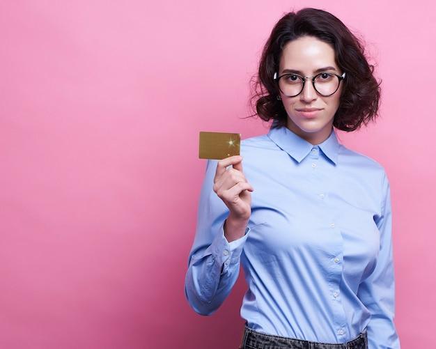 Portret van een gelukkige jonge vrouw in de zomerkleding en strohoed die plastic creditcard tonen terwijl het gebruiken van mobiele telefoon