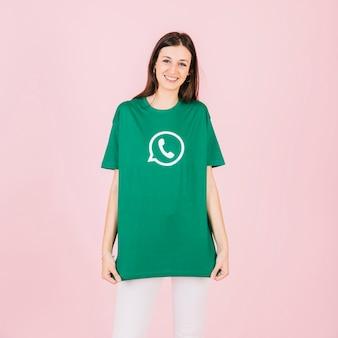 Portret van een gelukkige jonge vrouw in groene whatsapp t-shirt
