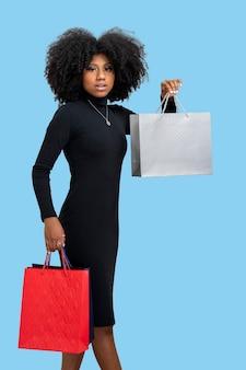 Portret van een gelukkige jonge vrouw met boodschappentas geïsoleerd op blauwe achtergrond
