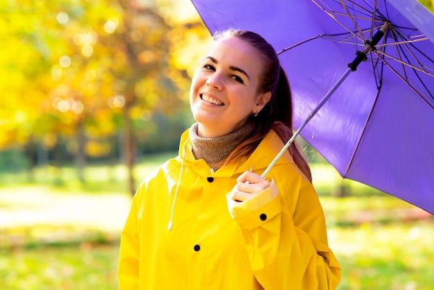 Portret van een gelukkige jonge vrouw met een paraplu glimlachend meisje dat in het park loopt