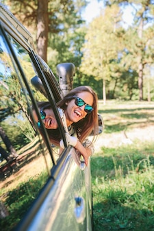Portret van een gelukkige jonge vrouw met een zonnebril die terugkijkt door de raamauto over een natuur