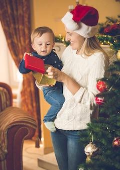 Portret van een gelukkige jonge vrouw met haar zoontje bij de kerstboom