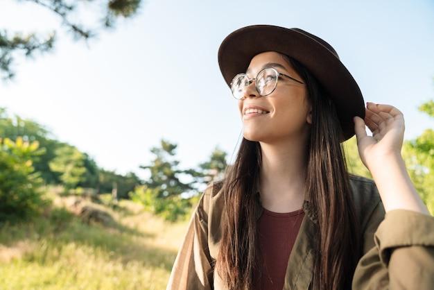 Portret van een gelukkige jonge vrouw met lang donker haar met een stijlvolle hoed en bril die op zonnige dag in een groen park loopt
