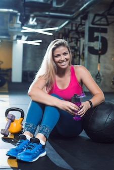 Portret van een gelukkige jonge vrouw met waterfles