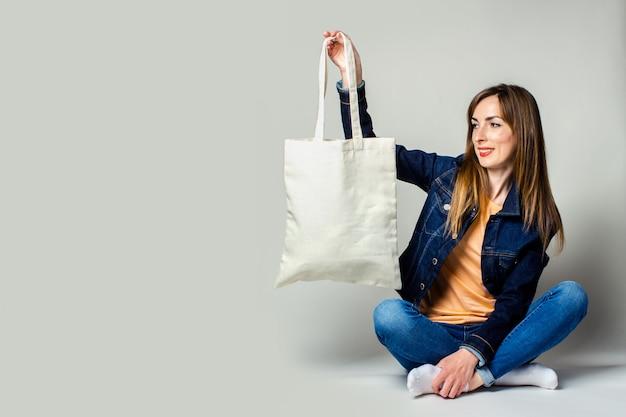 Portret van een gelukkige jonge vrouw zitten met gekruiste benen, met een linnen tas met aankopen op een lichte achtergrond