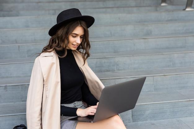 Portret van een gelukkige jonge vrouw, zittend op de trappen van de stad en met behulp van laptop buitenshuis