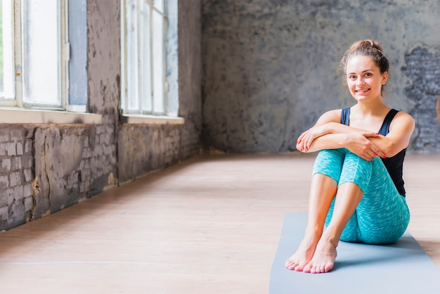Portret van een gelukkige jonge vrouw zittend op oefening mat
