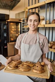Portret van een gelukkige jonge vrouwelijke bakker die op de werkplek staat en vers gebak verkoopt