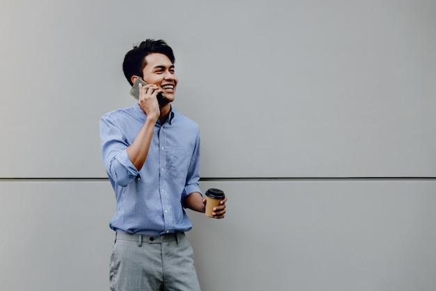Portret van een gelukkige jonge zakenman die mobiele telefoon met behulp van. levensstijl van moderne mensen. staan bij de muur met koffiekopje