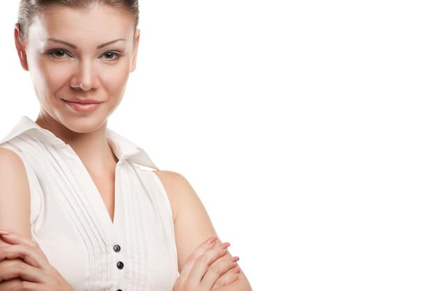 Portret van een gelukkige jonge zakenvrouw die zich met gevouwen hand tegen witte achtergrond bevindt