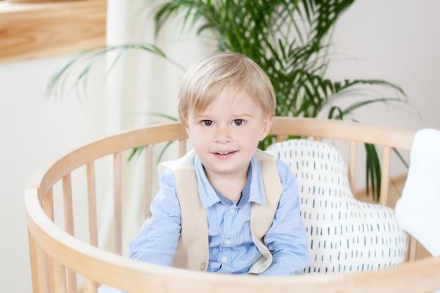 Portret van een gelukkige jongen die in een babywieg speelt. de jongen zit alleen in een wieg in de kinderkamer. een alleenstaand kind blijft thuis in een wieg. een kind in bed lacht, een jongen ligt in een wit bed in de kleuterschool.