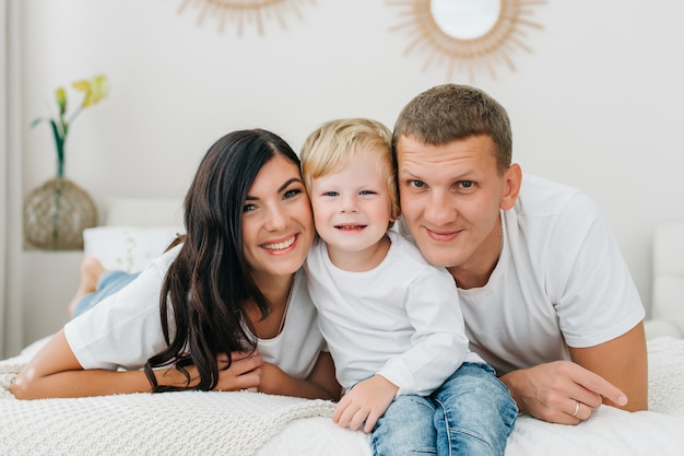 Portret van een gelukkige kaukasische op bed liggen en familie die terwijl thuis het bekijken camera in slaapkamer smacking.