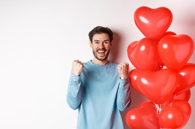 Portret van een gelukkige kerel die de dag van geliefden viert, in de buurt van valentijnsdag rood hart ballon staat en juicht, ja gebaar maakt en glimlacht naar de camera, staande op een witte achtergrond.