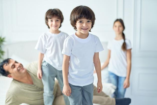 Portret van een gelukkige kleine latijns-jongen die naar de camera glimlacht terwijl hij thuis plezier heeft met zijn vader en broers en zussen. gelukkige jeugd, ouderschapsconcept