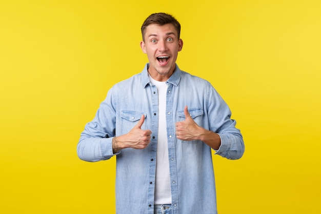 Portret van een gelukkige knappe blonde man die zijn duim omhoog steekt ter goedkeuring of die aanbeveelt om een geweldig super cool evenement bij te wonen. vrolijke opgewonden mannelijke klanten beoordelen geweldig product, gele achtergrond.