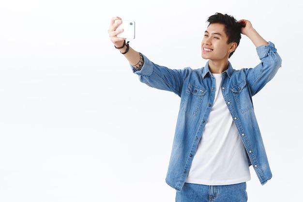 Portret van een gelukkige, knappe jonge aziatische man die een foto van zichzelf maakt met behulp van een smartphone, poseren en een vrolijke witte muur glimlachen