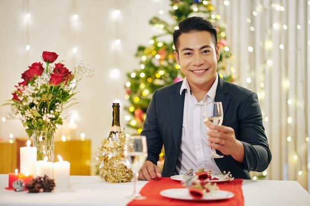 Portret van een gelukkige knappe jongeman die aan de kersttafel zit met een glas champagne