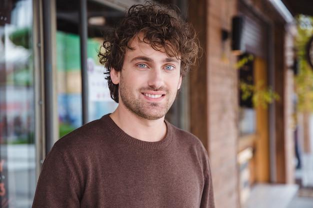 Portret van een gelukkige, knappe, positieve, aantrekkelijke, gekrulde lachende jongeman in een bruin sweetshirt in de stad