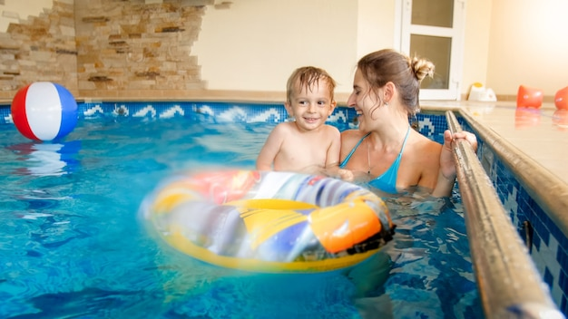 Portret van een gelukkige lachende peuterjongen met een jonge moeder die speelt met een kleurrijke opblaasbare strandbal in het zwembad in het zomerhotelresort