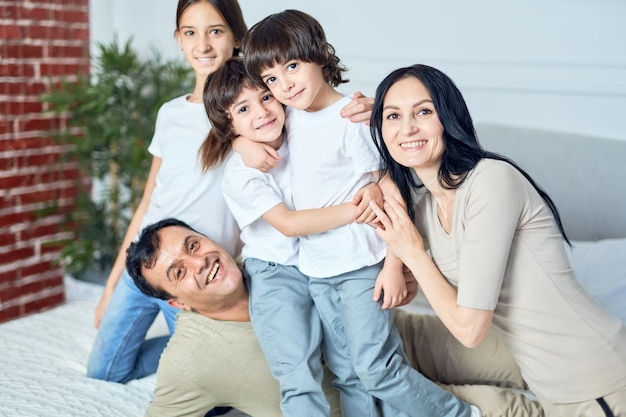 Portret van een gelukkige latijnse familie, ouders en kinderen die naar de camera glimlachen terwijl ze thuis tijd doorbrengen. gelukkige jeugd, ouderschapsconcept