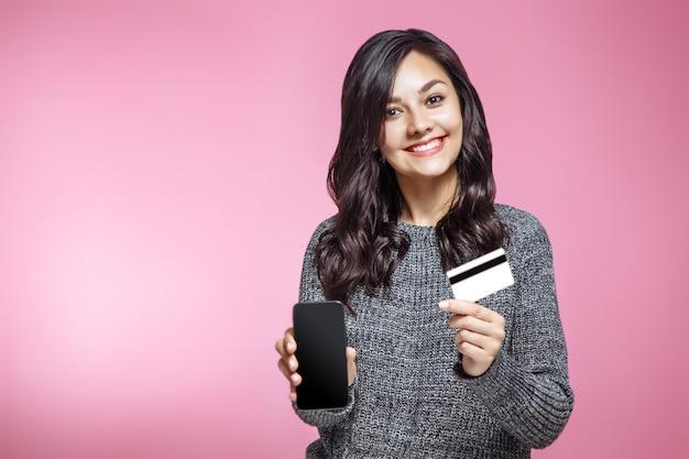 Portret van een gelukkige lege het scherm mobiele telefoon van de meisjesholding en het tonen van creditcard die over roze achtergrond wordt geïsoleerd